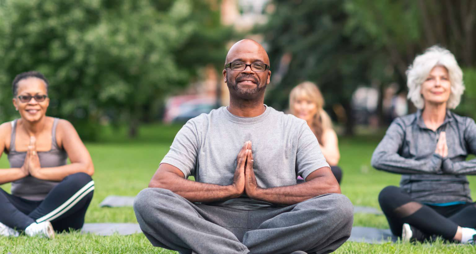 community wellness program with people meditating in the park